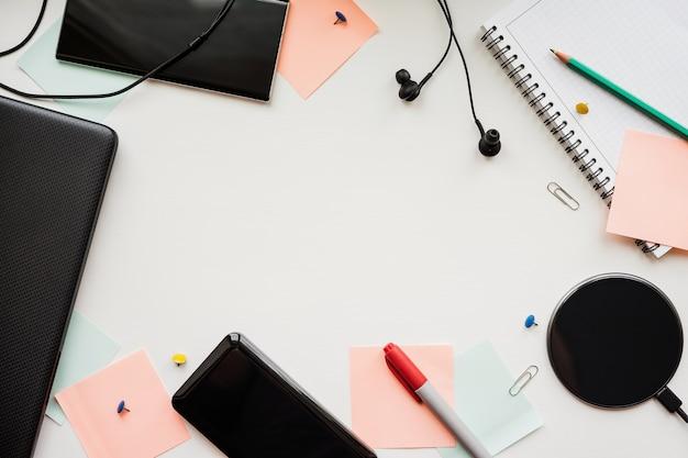 Laptop, smartphone, banco de energia, carregamento sem fio, fones de ouvido e artigos de papelaria em uma mesa branca.