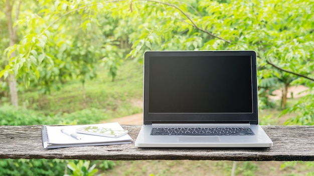 Laptop, smartphone, caneta e livro na mesa de madeira.
