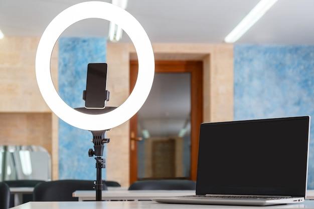 Laptop smartphone tela de exibição vazia modelo da web anel lâmpada luz vlogger blogger estúdio espaço de trabalho sala de reuniões sem ninguém equipamento para streaming online apresentação de trabalho remoto