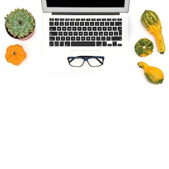 Laptop, suculenta, abóbora de outono em fundo branco. local de trabalho de escritório. postura plana