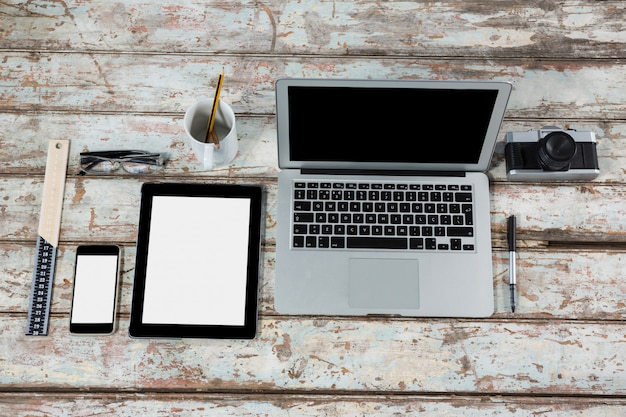 Laptop, tablet digital, smartphone e câmera com acessórios de escritório