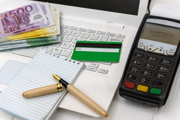Laptop, terminal com cartão de crédito e euro em rolo