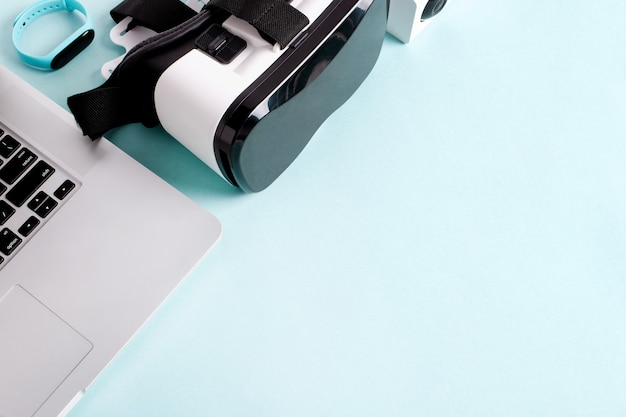 Laptop, vr, câmera ip e relógios inteligentes na mesa azul com copyspace