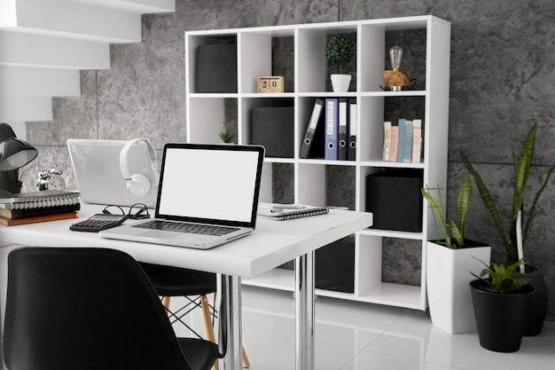 Laptops em mesas com cadeiras no escritório