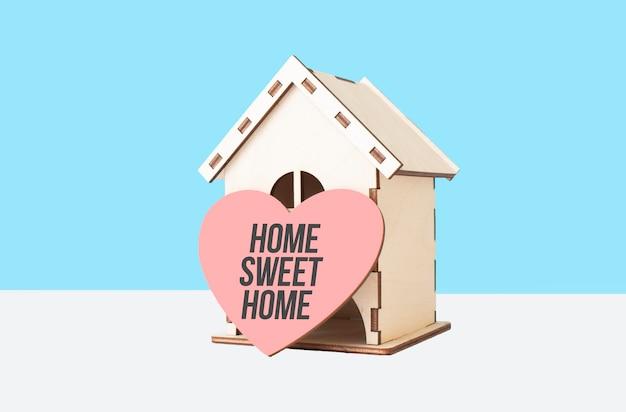 Lar doce lar palavra no modelo de coração de madeira e casa de madeira sobre fundo azul.