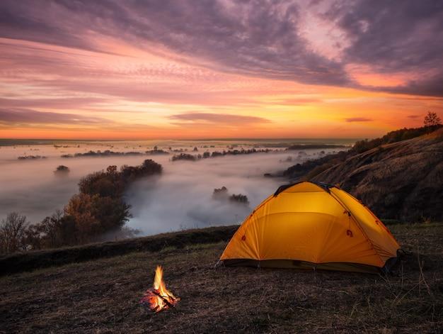 Laranja acesa dentro da barraca e fogo sobre o rio enevoado ao pôr do sol