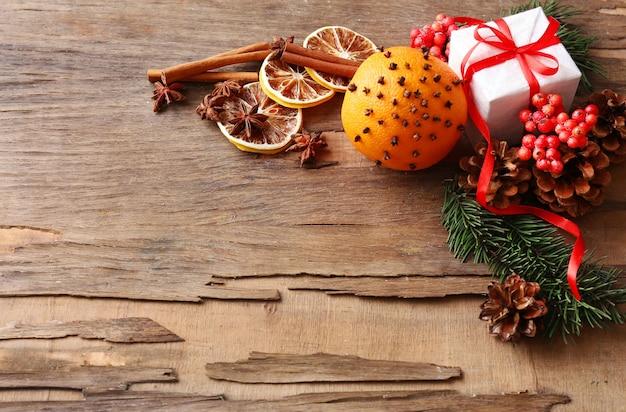 Laranja com caixa de presente, especiarias, rodelas de limão seco e raminhos de árvore de natal em fundo de madeira rústico