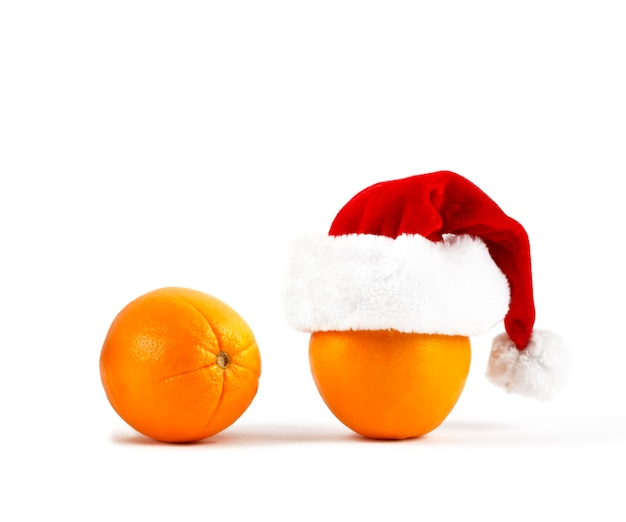 Laranja com chapéu de papai noel. natal ou ano novo com laranjas.