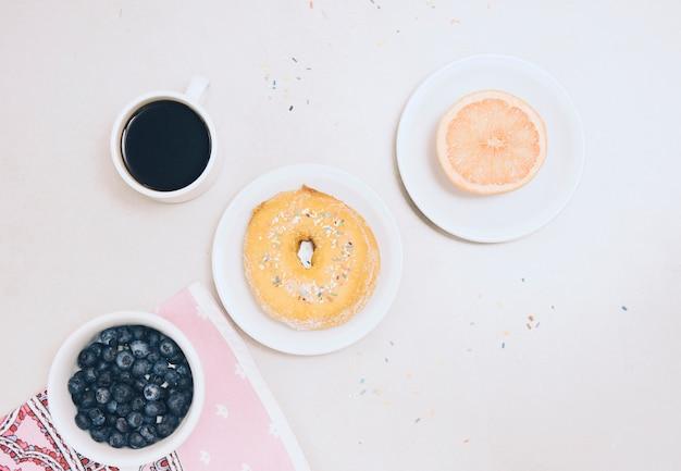 Laranja cortada ao meio; amoras; xícara de café e mirtilos em fundo branco