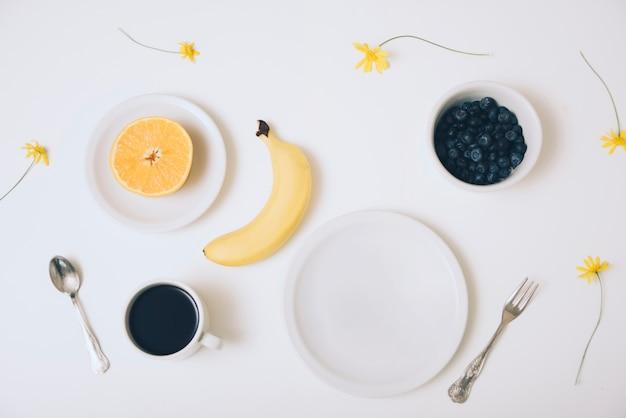 Laranja cortada ao meio; banana; tigela de mirtilos; xícara de café e um prato vazio no fundo branco
