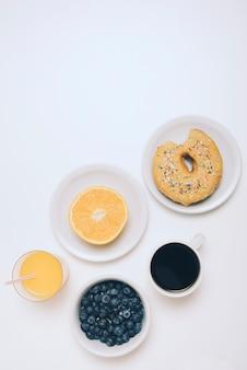 Laranja cortada ao meio; suco de laranja; amoras; xícara de café e comido donut no fundo branco