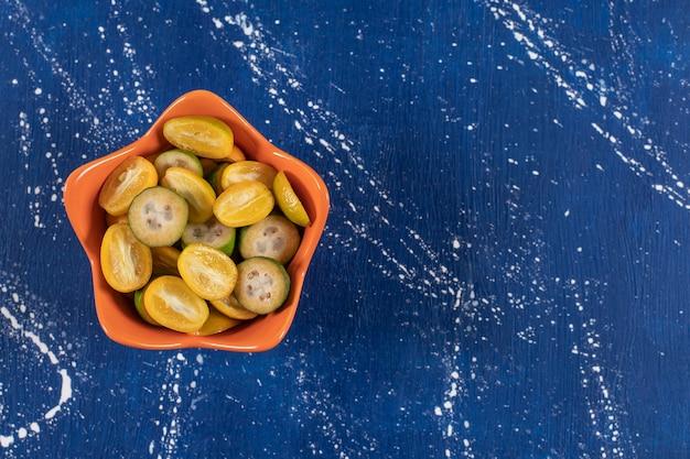 Laranja de frutas fatiadas de kumquat e feijoa em superfície de mármore.