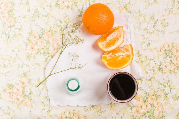 Laranja e fatia inteiras; xícara de café; gypsophila e garrafa de leite em pano de fundo floral