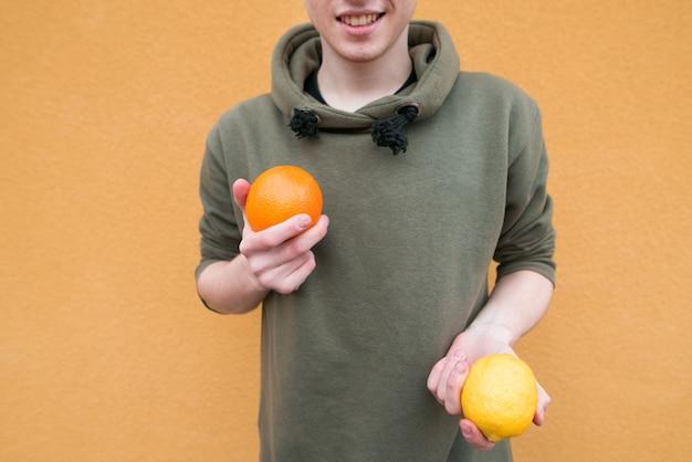 Laranja e limão nas mãos de um jovem de pé em uma parede laranja. concept fruit
