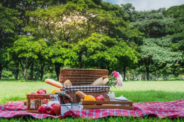 Laranja e maçã, frutas frescas na cesta de rattan, pão e bebida é preparado para piquenique.