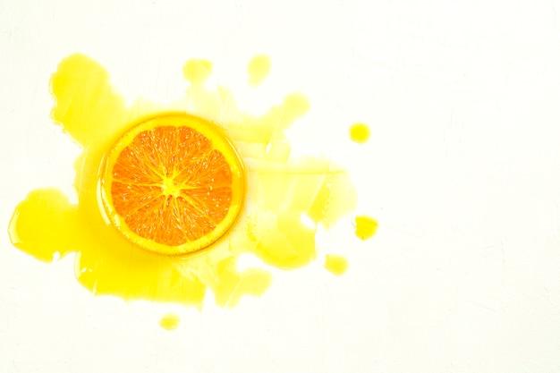 Laranja fatiada e suco de laranja se espalhando sobre um fundo branco