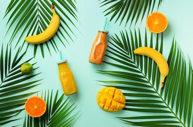 Laranja fresca, banana, abacaxi, manga batido e frutas suculentas em folhas de palmeira. bebida de verão de desintoxicação. conceito vegetariano.