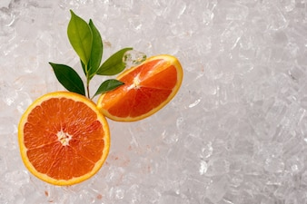 Laranja fresca e laranja cortada em fundo de tubo de gelo