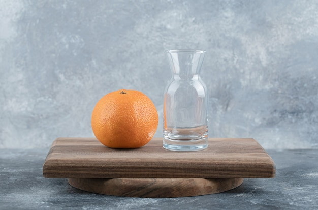 Laranja fresca e vidro na placa de madeira.