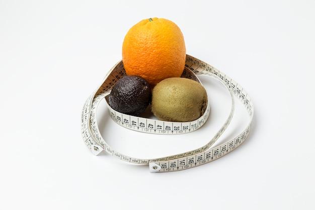 Laranja, kiwi e abacate rodeado por uma fita métrica