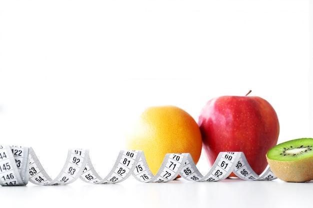 Laranja, kiwi e maçã rodeada por uma fita métrica