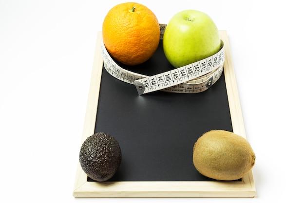 Laranja, maçã, kiwi e abacate rodeado por uma fita métrica