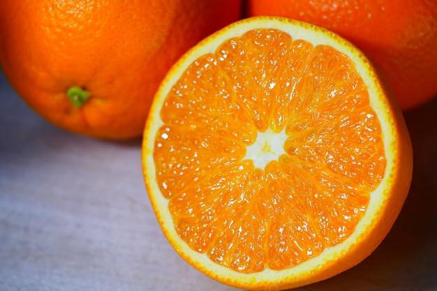 Laranja, metade da laranja na mesa de madeira