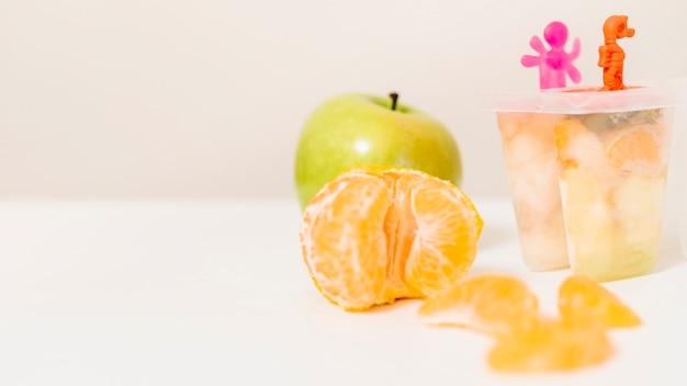 Laranja; molde de maçã e picolé na mesa