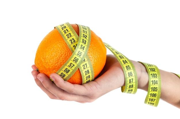 Laranja na mão com fita métrica em fundo branco, alimento saudável