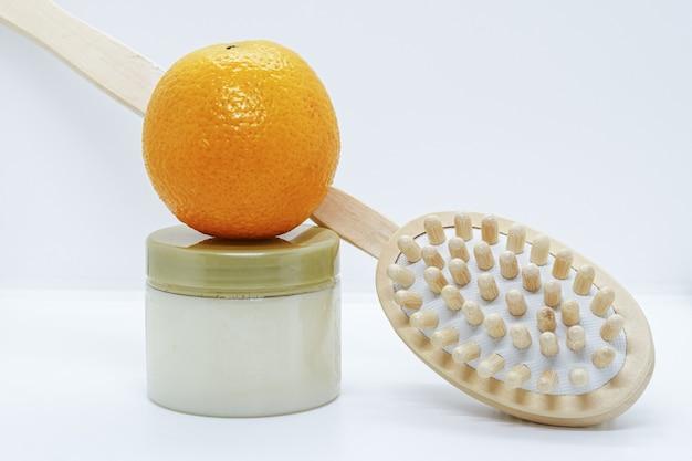 Laranja no frasco de esfoliante corporal e escova de massagem dupla face para corpo em fundo branco