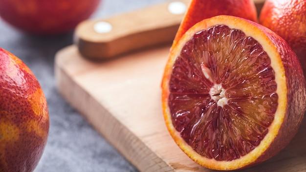 Laranja pigmentada na tábua de madeira. laranja vermelha.