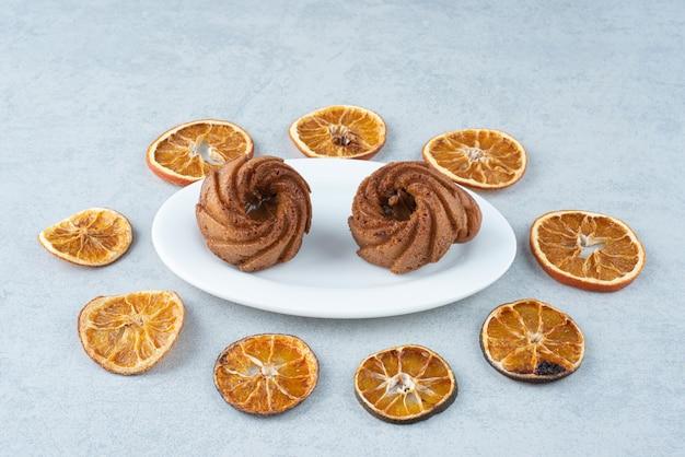 Laranja seca com dois deliciosos cupcakes em fundo branco