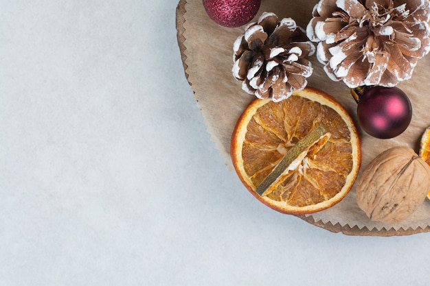 Laranja seca com pinhas e bolas de natal na placa de madeira. foto de alta qualidade