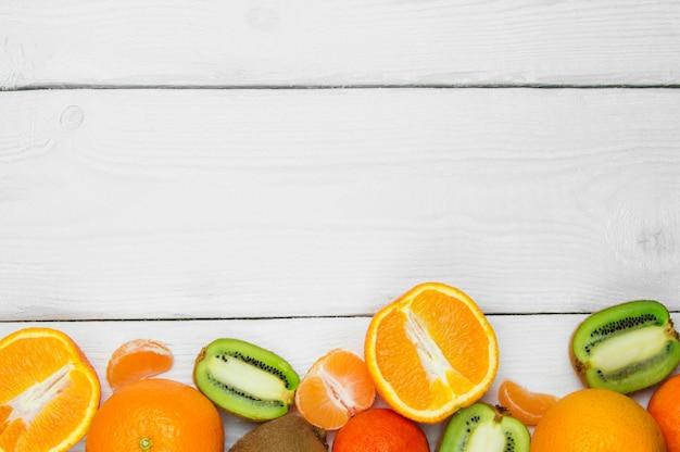 Laranja, tangerina e kiwis de frutas na superfície vintage de madeira branca