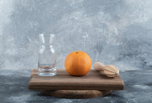 Laranja única, escareador e vidro na placa de madeira.