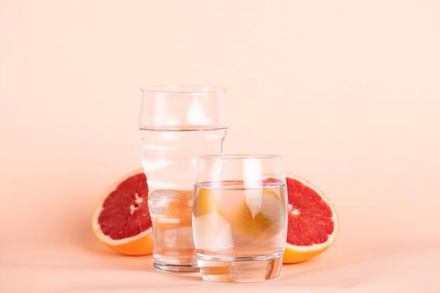 Laranja vermelha cortada com copos de água