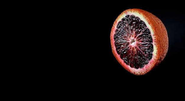 Laranja vermelha siciliana madura e meio suculenta no escuro