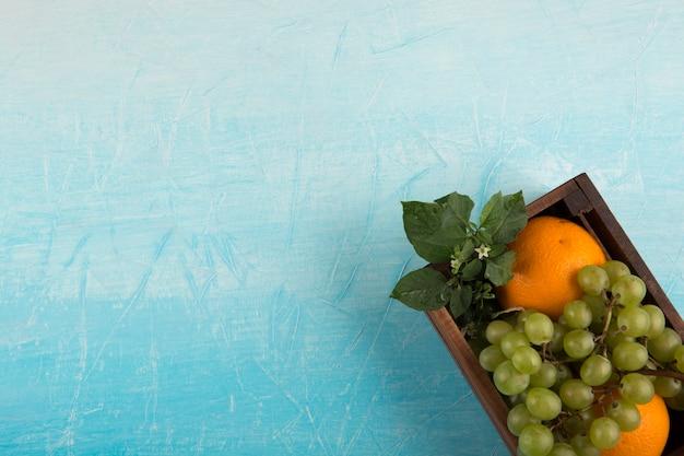 Laranjas amarelas e um cacho de uva em uma caixa de madeira no canto