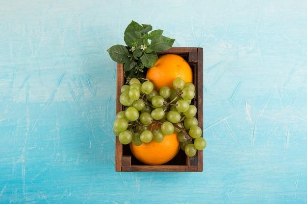Laranjas amarelas e um cacho de uva em uma caixa de madeira no centro