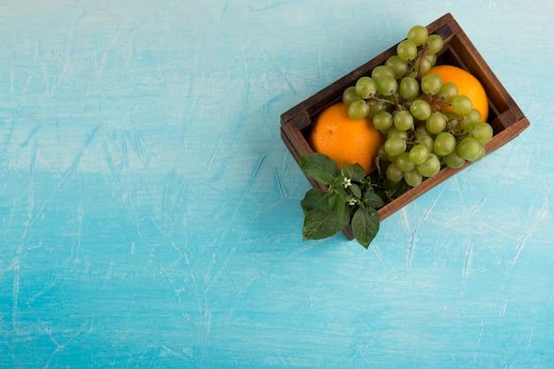 Laranjas amarelas e um cacho de uva em uma caixa de madeira