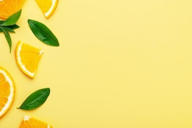 Laranjas com fatias e pedaços com folhas em um fundo amarelo. suculentas frutas cítricas orgânicas de verão com vista superior de vitamina c, copie o espaço.
