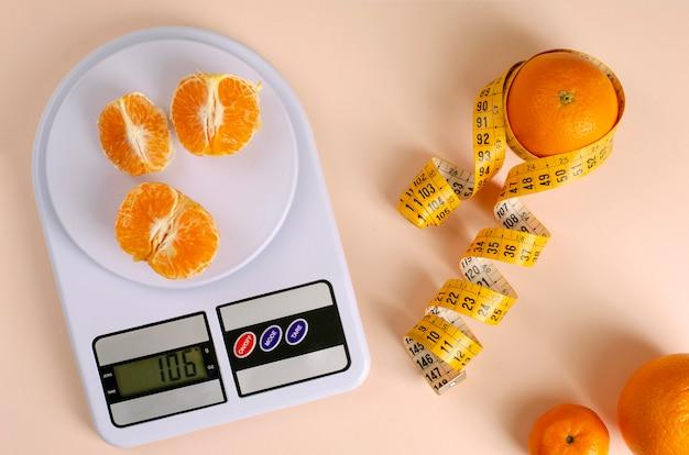 Laranjas com fita métrica e balanças de cozinha digital.