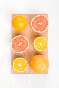 Laranjas cortadas ao meio e toranjas na tábua de cortar sobre a mesa branca