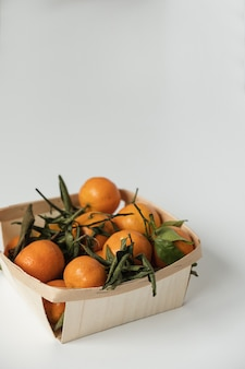 Laranjas cruas, frutos de tangerina com folhas verdes em uma cesta em branco