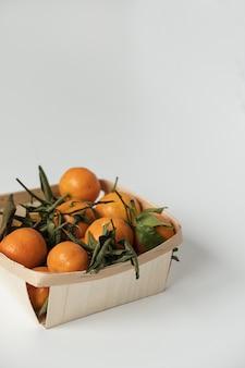 Laranjas cruas, tangerinas com folhas verdes em uma cesta em branco