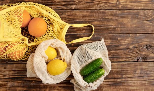 Laranjas de frutas e legumes frescas, limões, pepinos em sacos de algodão reutilizáveis ecológicos, biodegradáveis em uma mesa de madeira, parede com espaço de cópia. responsabilidade socioambiental plana.