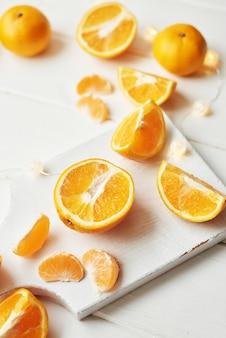 Laranjas de natal e tangerinas em um branco perto da janela
