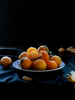 Laranjas de tangerina espanholas frescas frutas com folhas na mesa rústica, estilo escuro e temperamental
