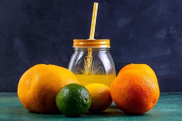 Laranjas de vista frontal com limão limão e suco de laranja em uma jarra