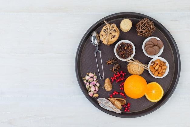 Laranjas e biscoitos na bandeja com coador de chá, ervas e especiarias